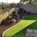 small backyard landscape with synthetic lawn